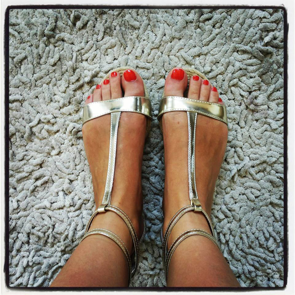 Beautiful girl with golden sandals and red pedicure
