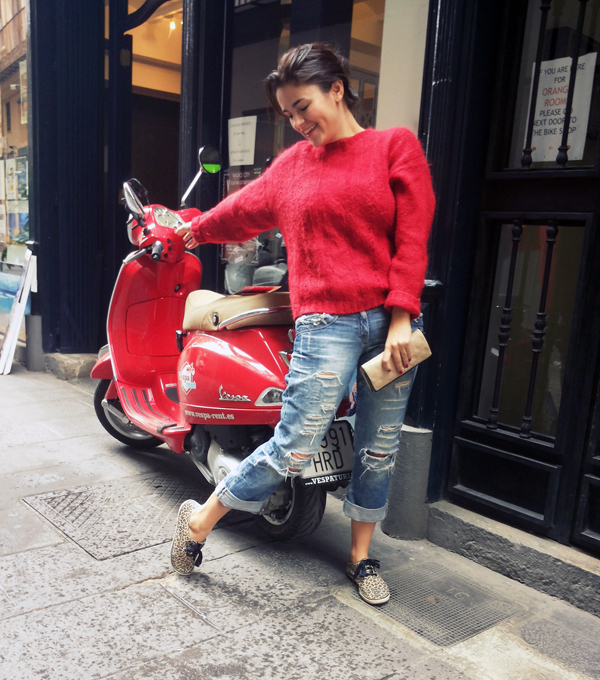 Girl in jeans wearing red sweater next to a vespa