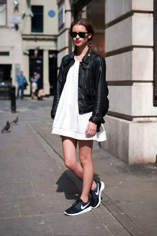 Model on the street in black running shoes from nike with white dress and black leather jacket