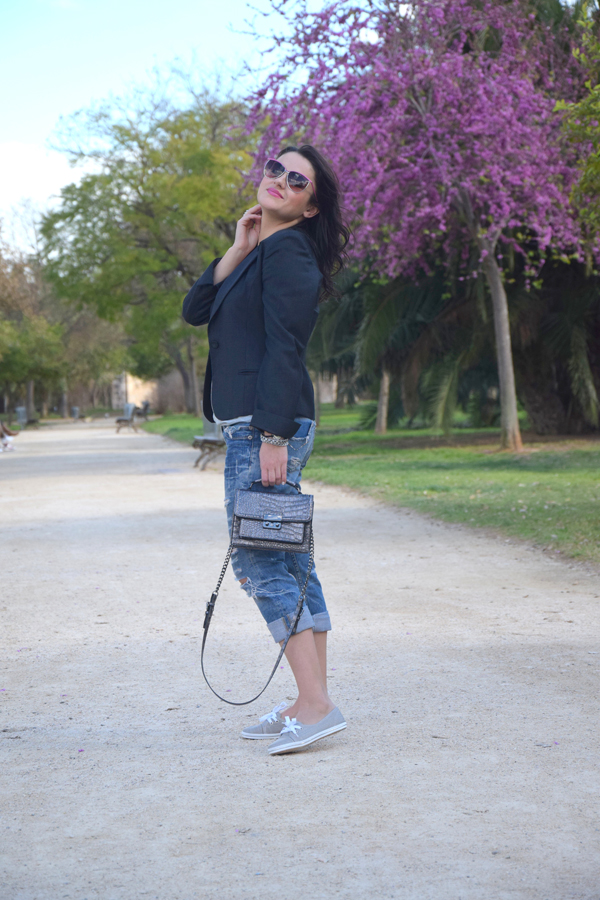 Fashion advisor posing in park wearing Mango bag, ripped jeans in tomboy look, and blazer from Zara