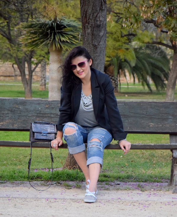 Fashion blogger posing in boyfriend jeans and grey sneakers on a bench with a mango bag