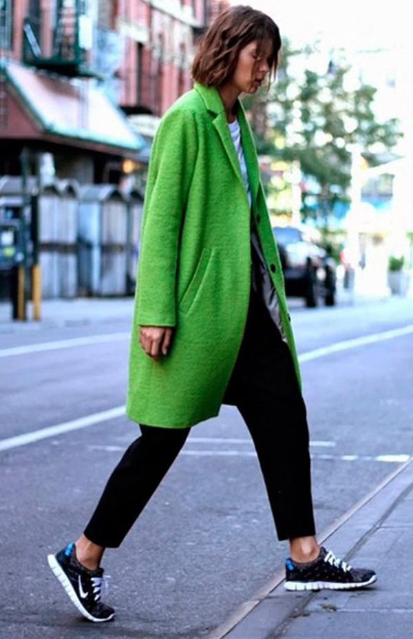 Girl in Nike's wearing a green coat
