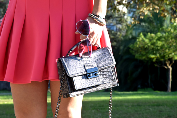 Chanel handbag and pink skirt with pink sunglasses from Michael Kors.