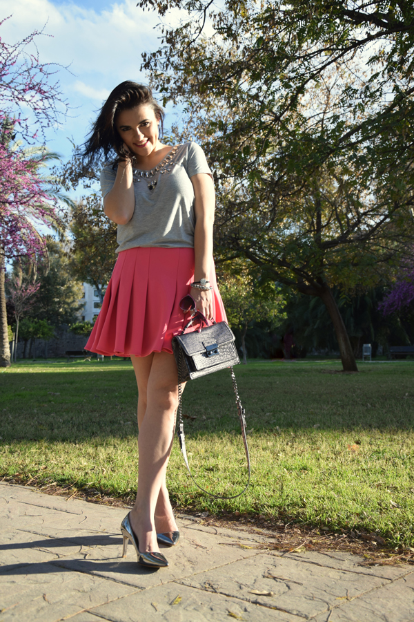 Beautiful young lady wearing pink skirt from HM, grey shirt and Chanel bag in the park.
