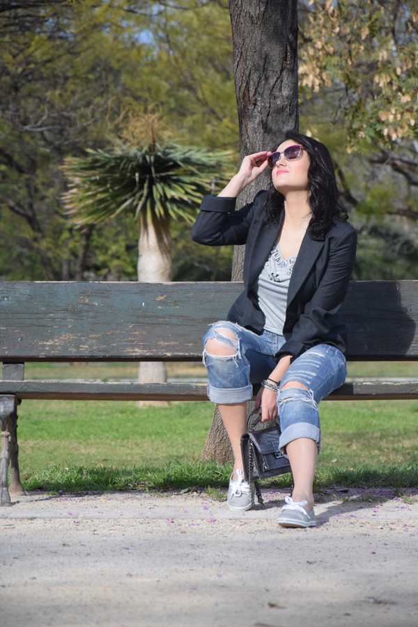 A beautiful girl staying on the bench in the park looking at the sun dressed in ripped jeans and grey t-shirt