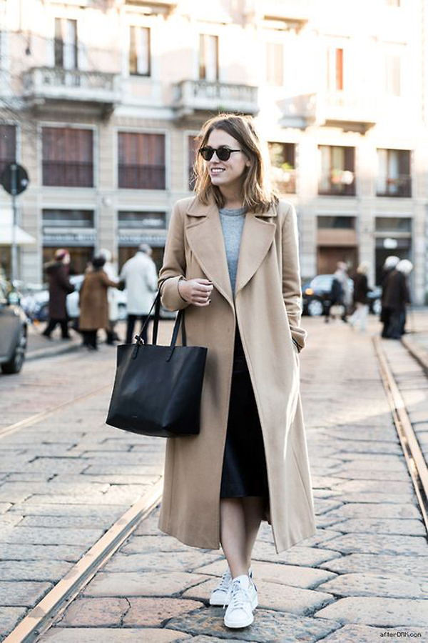 Fashion blogger in white running shoes and beige coat offering style tips