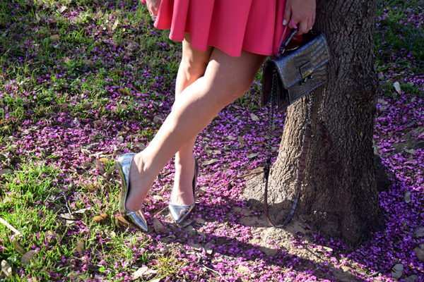 Silver shoes in beautiful park with many beautiful pink flowers