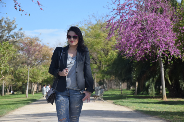 Girl in ripped jeans and grey blazer with Mango bag staying in the park with beautiful trees in spring time