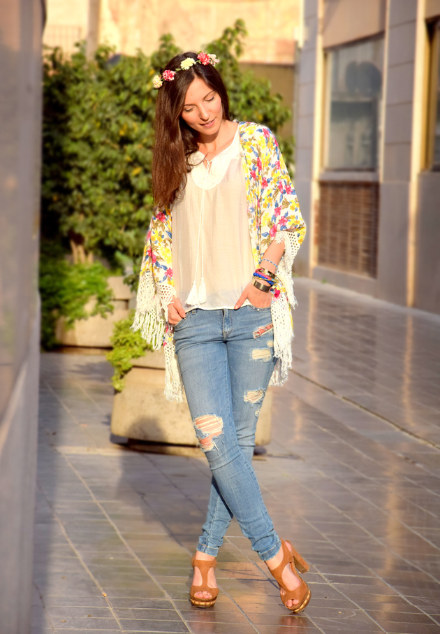 Hippie girl in a boho chic style wearing distressed jeans, Kimono with fringe and Zara flower crown