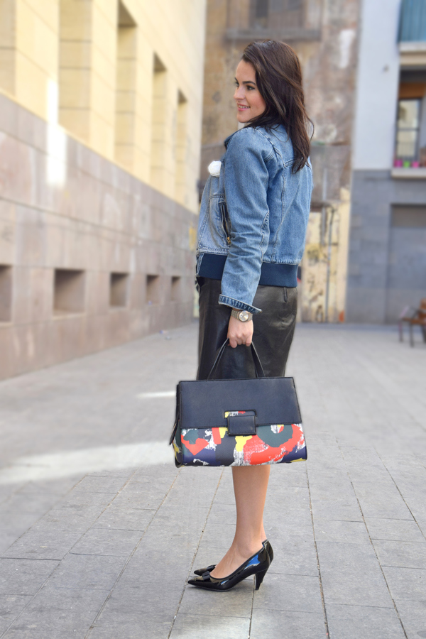 Lady staying on the street with leather skirt, denim jacket and colorful handbag