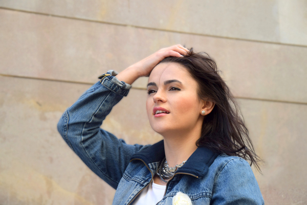 Girl with her hair in the wind wearing a denim jacket and white tee