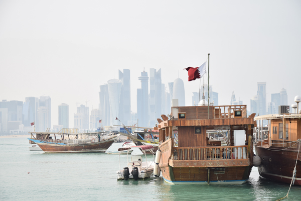 boat and skyline of doha, qatar from al corniche with the qatar flag