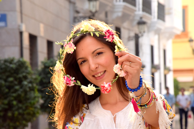 Girl with flower crown in her hands and many bracelets