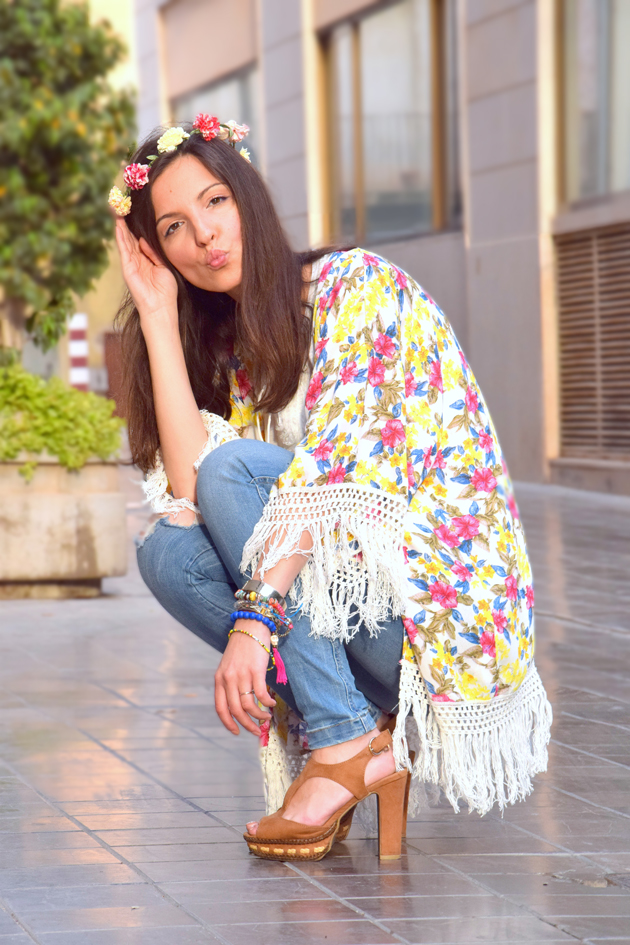 Girl giving a kiss wearing flowers in her hair, ripped jeans and white blouse. She is a style advisor