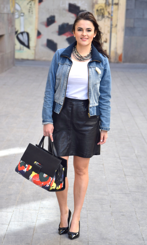 A woman smiling, wearing a denim jacket, leather skirt, and a white t-shirt