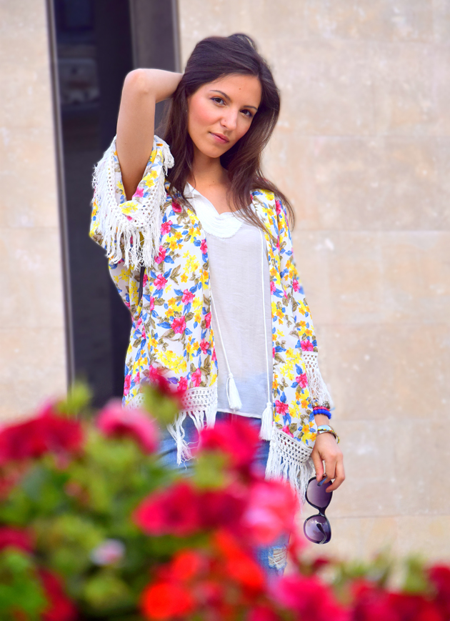 Beautiful girl wearing kimono from Zara and Chanel bag staying among flowers.