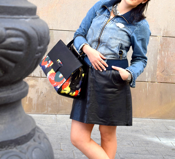 A girl standing next to a wall wearing denim, leather and a bag from Chanel