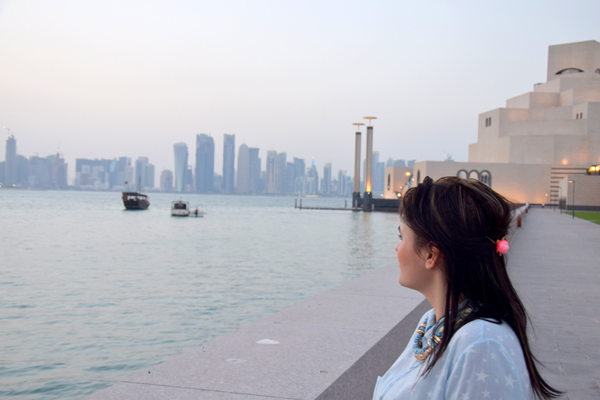 girl watching skyline in qatar, doha in front of muslim art museum