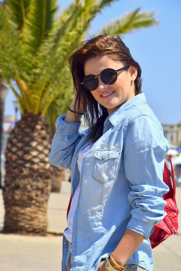 Beautiful girl smiling with sunglasses and wearing a denim shirt