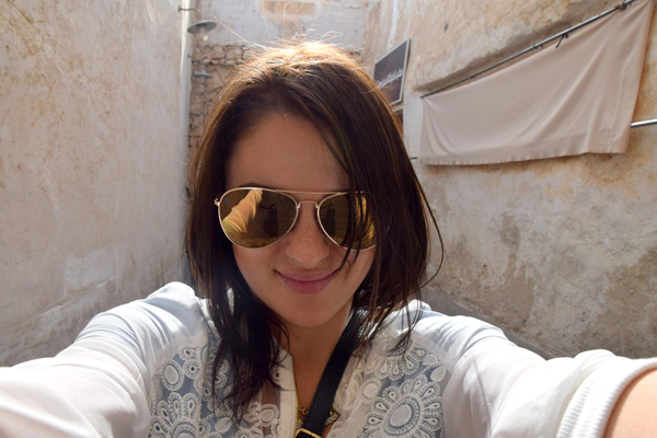 western woman in souk waqif wearing sunglasses and white blouse in doha qatar