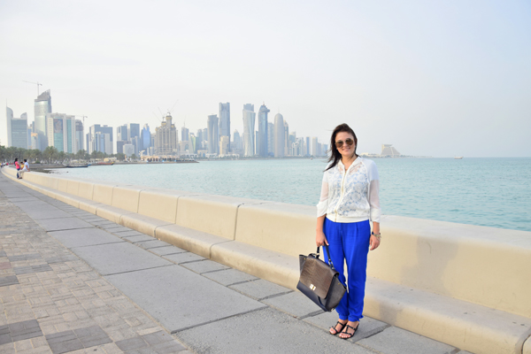 woman posing in doha, qatar in white blouse and blue pants chanel and dior bag