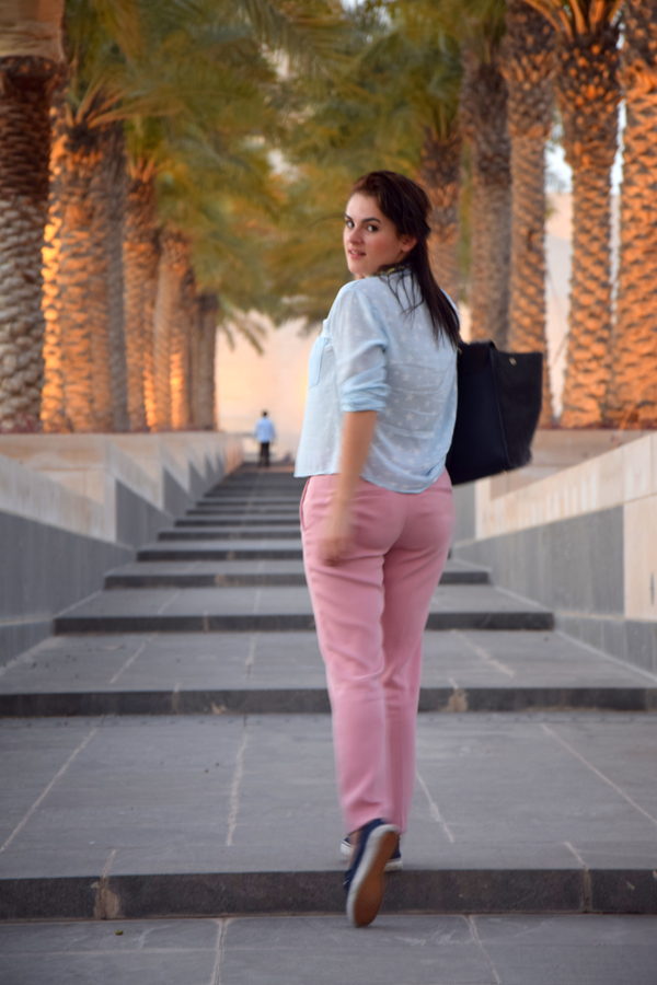 girl walking in doha, qatar wearing pink trousers and blue shirt fashion in gatar