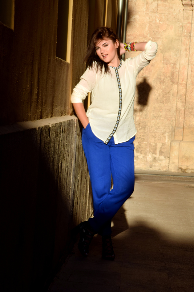 Beautiful girl in white ethnic blouse from Mango and blue trousers from H&M staying in the sunset