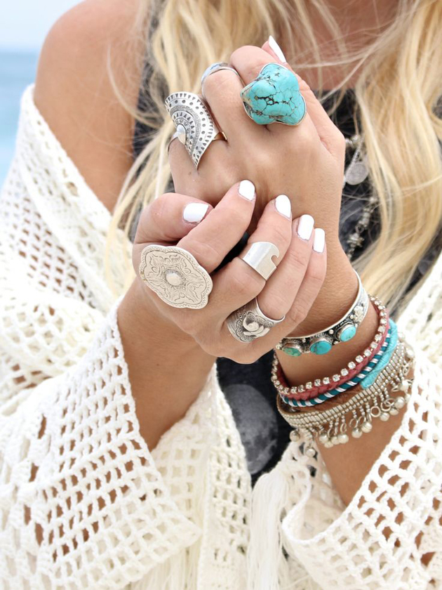 two hands of a girl with white nail polish and turquoise jewelry
