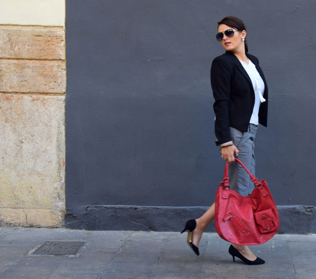girl waking wearing black shoes, grey bermuda shorts, white blouse and a black blazer for office. she is a style advisor
