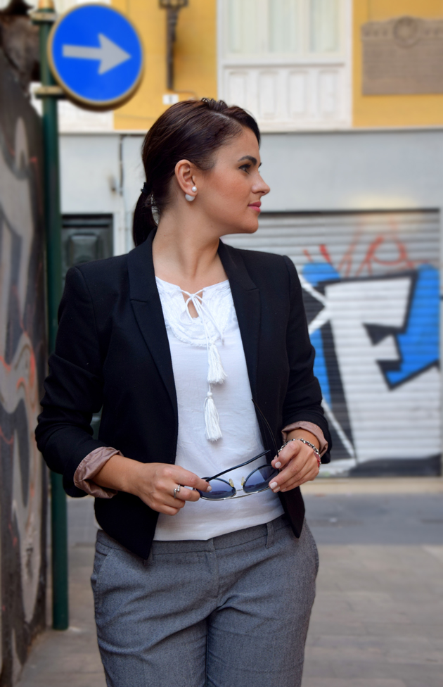 elegant woman wearing a black blazer, white shirt and dior earrings. she has a business style