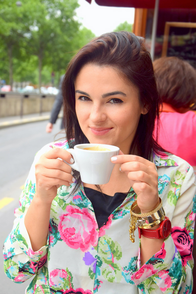 girl smiling and drinking coffee in Paris. She is wearing a floral dress and Michael Kors bag