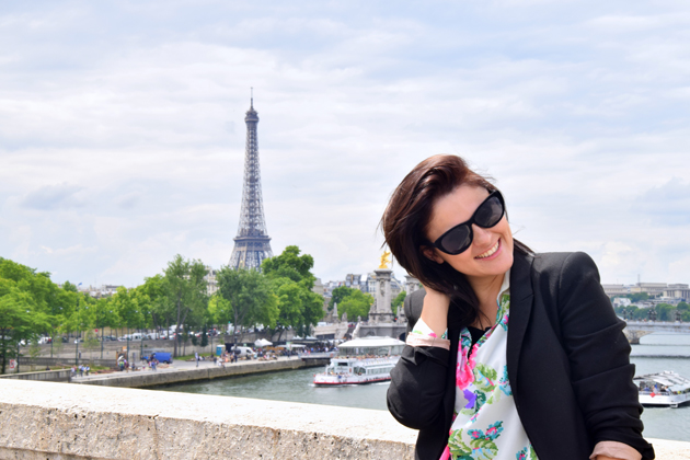 woman smiling wearing sunglasses and behind her you can see eiffel tower