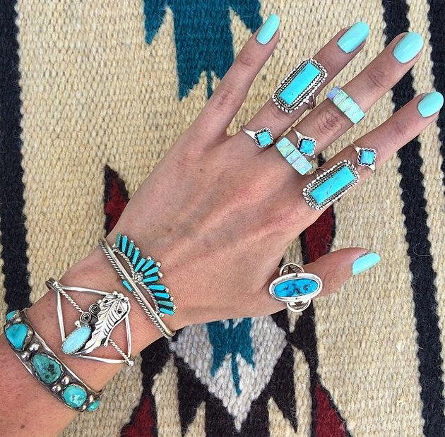 hand with many rings and bracelet with turquoise in boho chic style