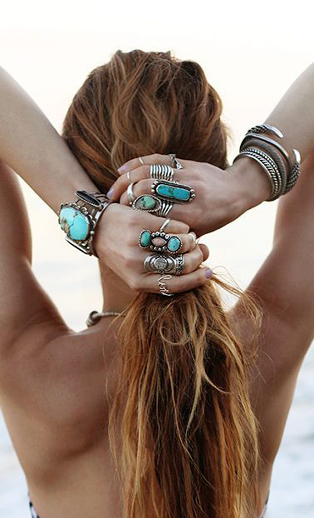 woman with long hair and many bracelets with turquoise as a gypsy