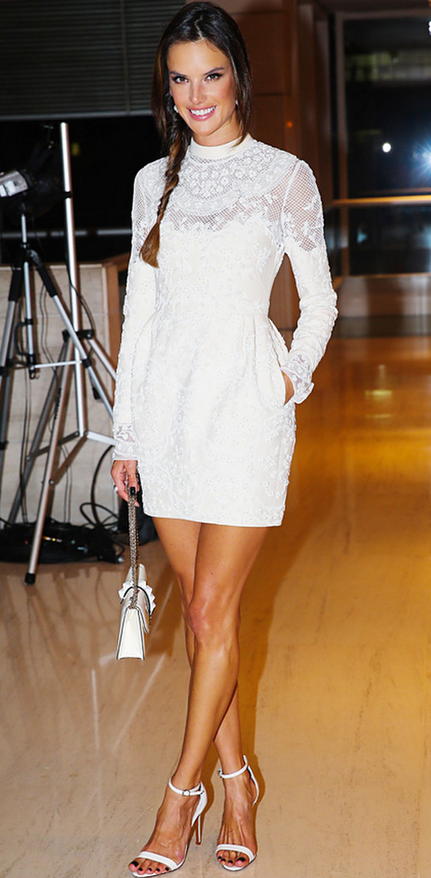 alessandra ambrosio in white dress and white sandals. she has her hair in a ponytail.