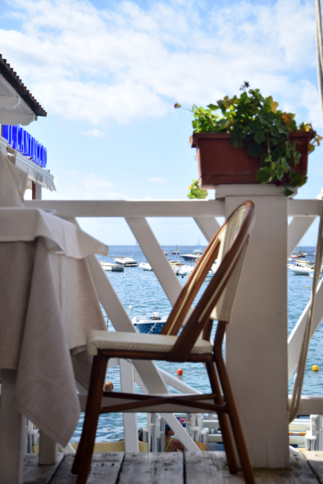 beautiful place on the beach in Italy. There is a chair and flowers on the dock of a Italian restaurant