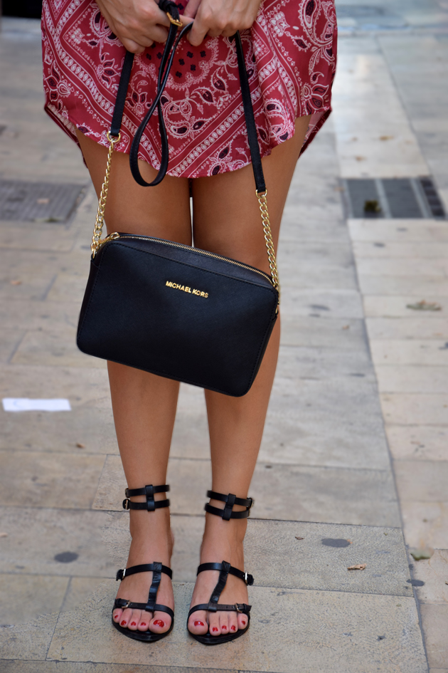a lady having a Michael Kors handbag and black sandals. She has sexy legs