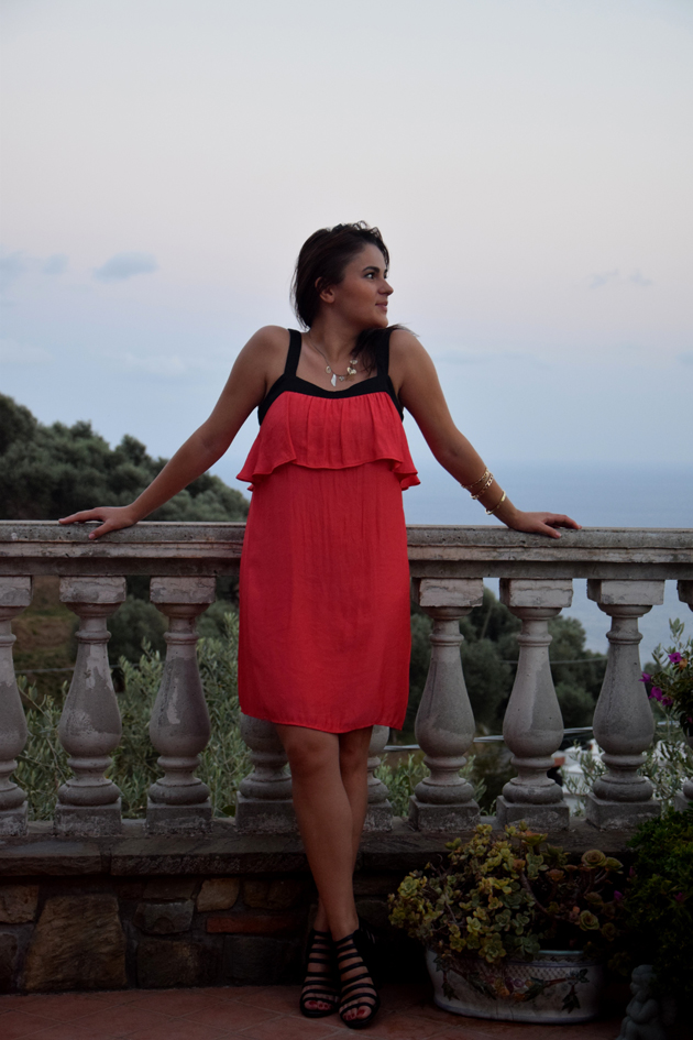 woman wearing red dress and black sandals. she is having many golden bracelets and she is posing on a terrace with sea view