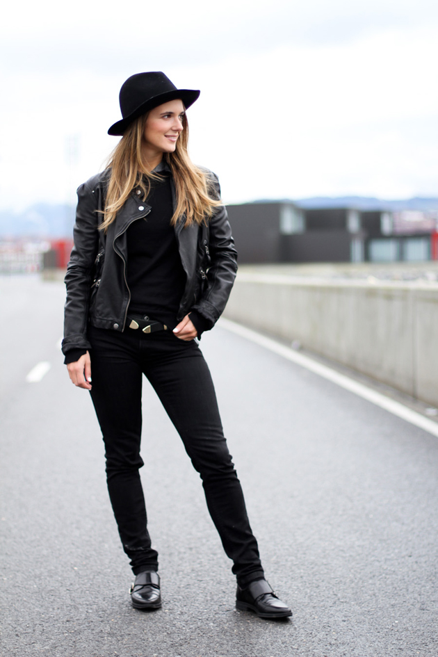 A girl on the street looking very taller. She is wearing only black clothes