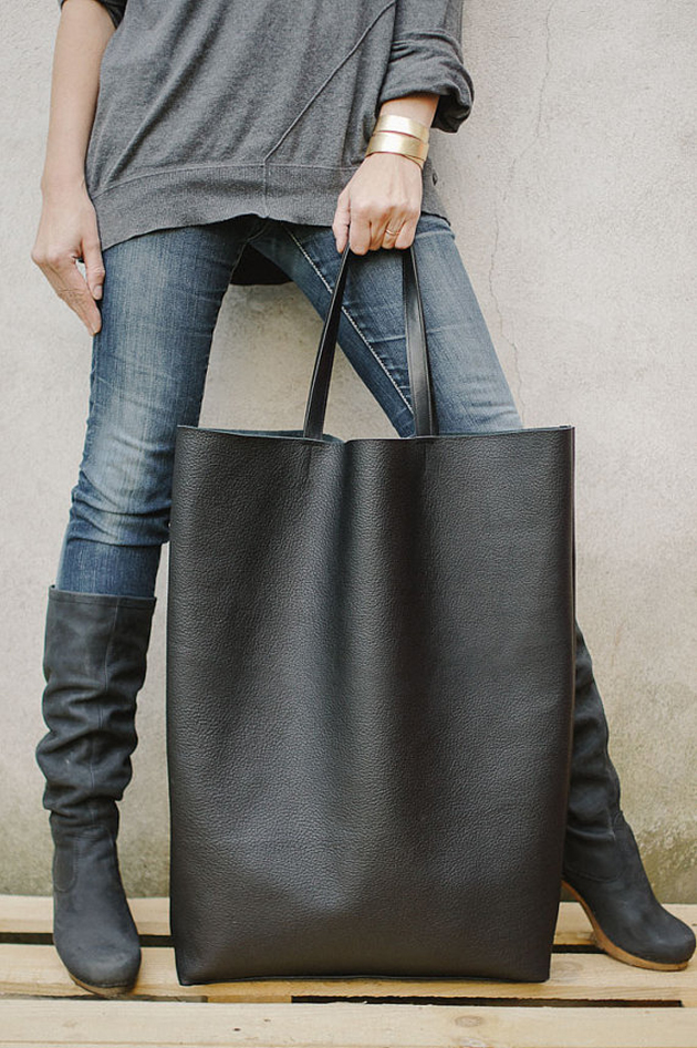 a woman with a very big black bag. she is having a great bracelet and blue jeans
