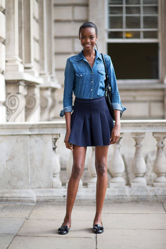 a black woman wearing a denim shirt and a skirt with sneakers