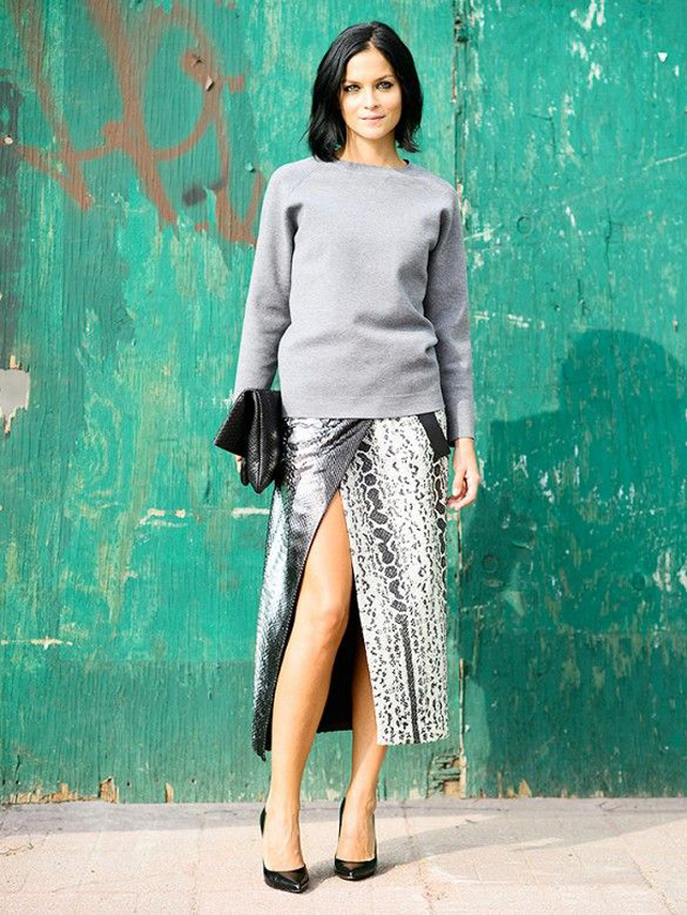 a woman wearing a great grey sweater and a sexy skirt. She is walking on the street during NYFW