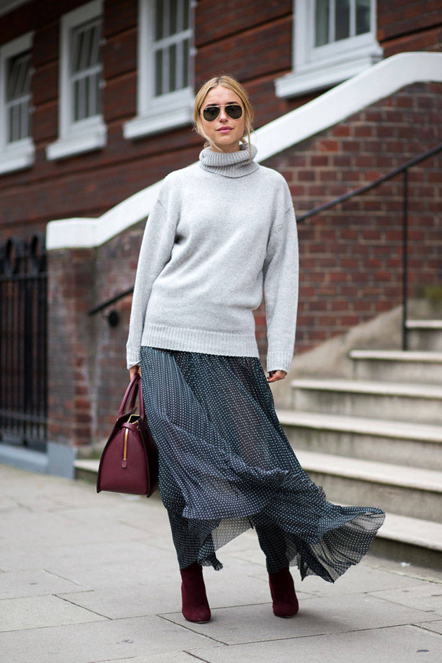 a beautiful woman wearing a long skirt and a grey sweater for autumn.