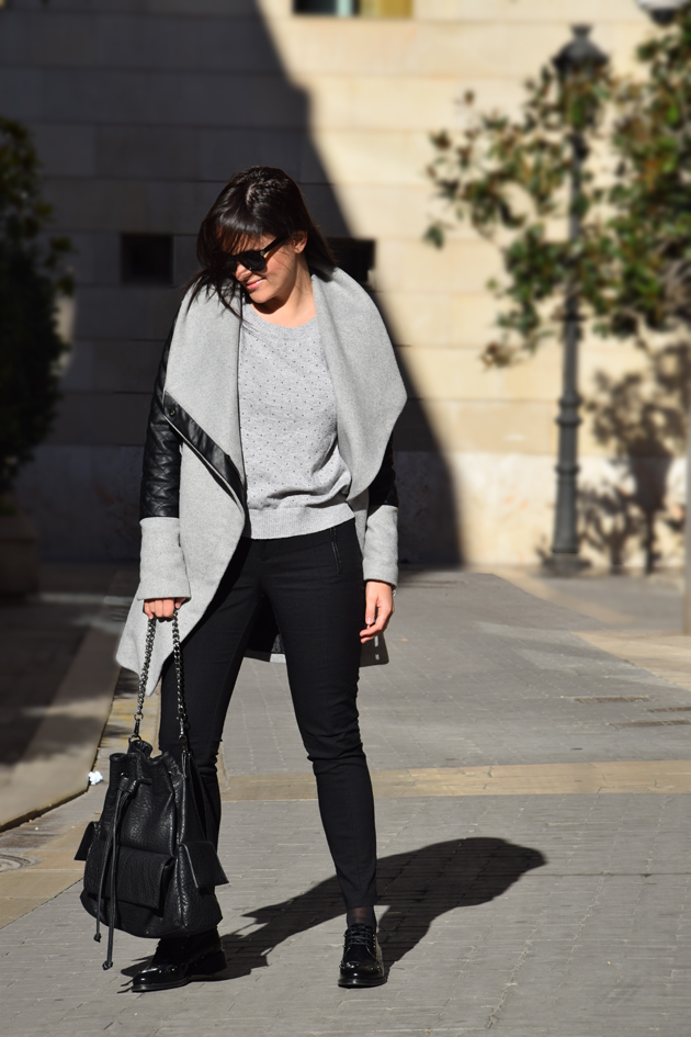 woman wearing a grey and black outfit. She is wearing coat from Bershka, shoes from Net-a-Porter