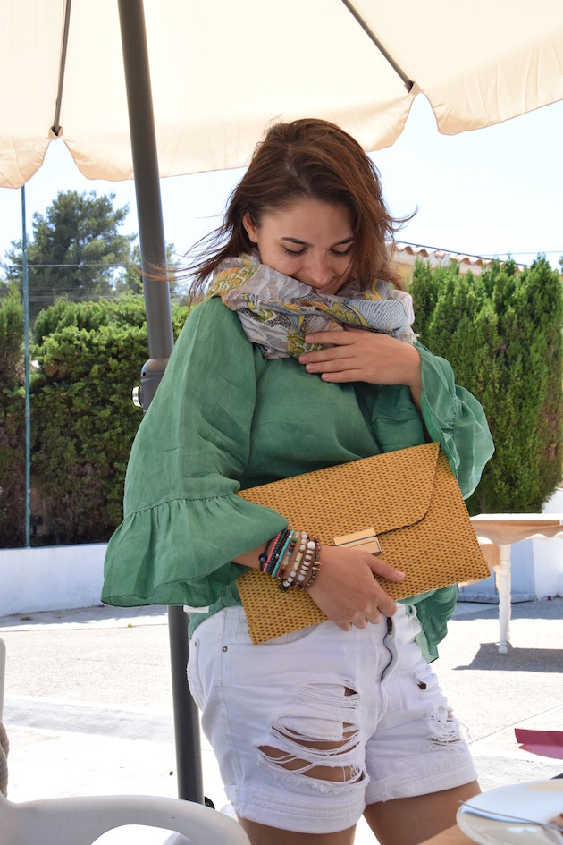 girl wearing a green silk top and denim