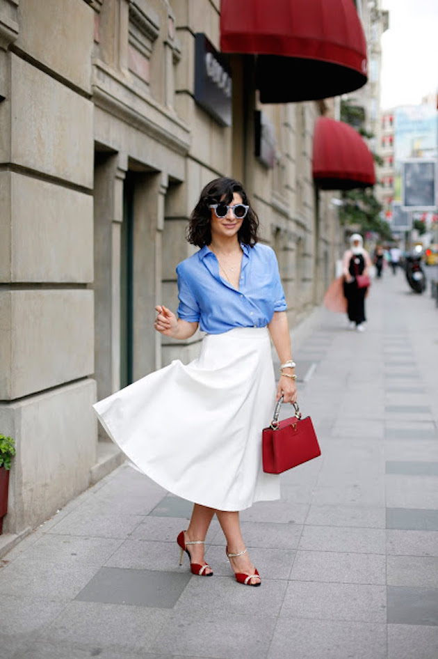 girl wearing midi white skirt and blue shirt with red heels
