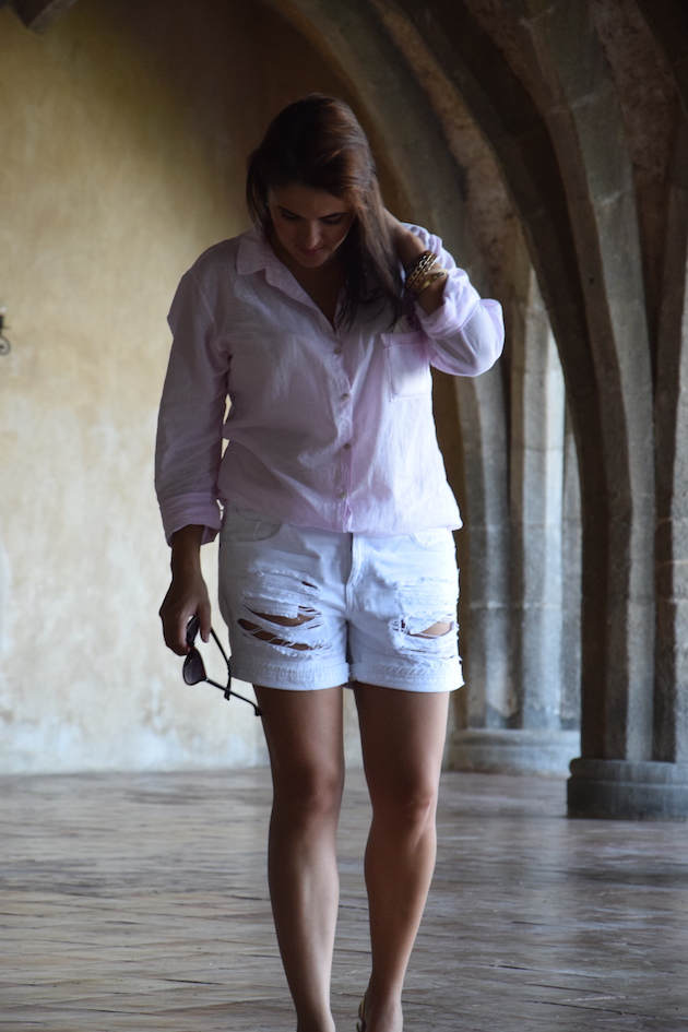a woman wearing shite shorts and a shirt. She is a casual look