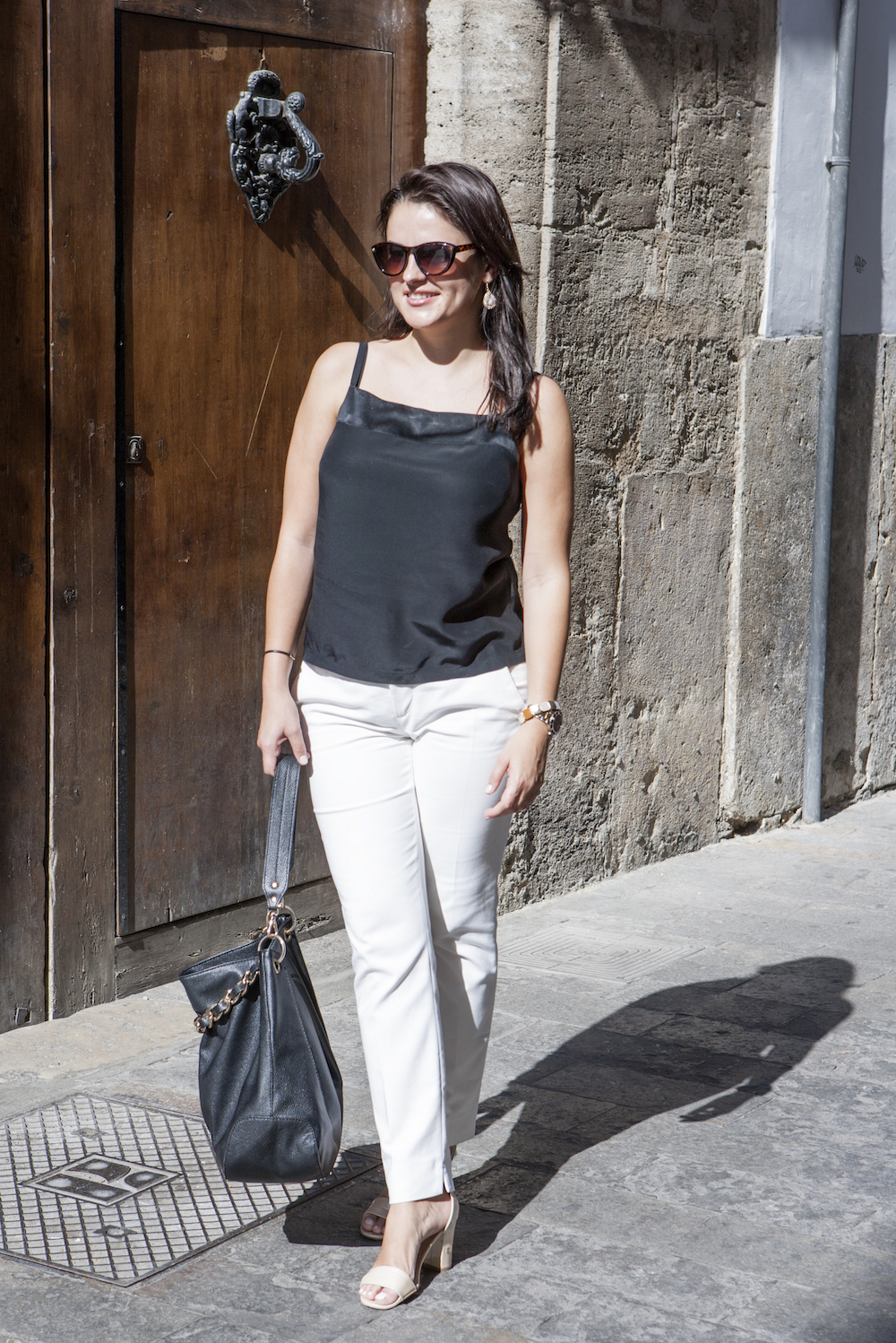 woman wearing white pants and black top going to the office: office wear for summer
