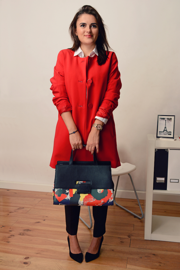 a woman wearing a red coat in her office