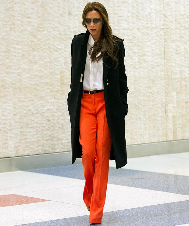 victoria beckham in red pants and black coat
